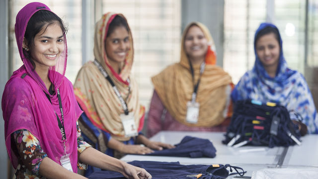 4 woman smiling working with garments with girl in pink