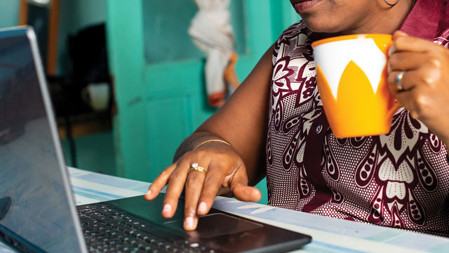 woman holding yellow coffee mug using a laptop