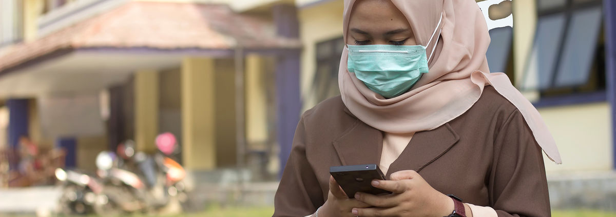 woman with pink scarf wearing mask looking at mobile phone