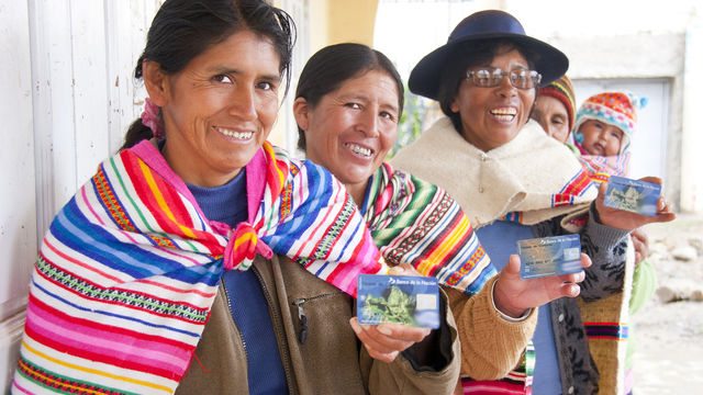 four mexican women standing smailing holding visa credit cards with a baby