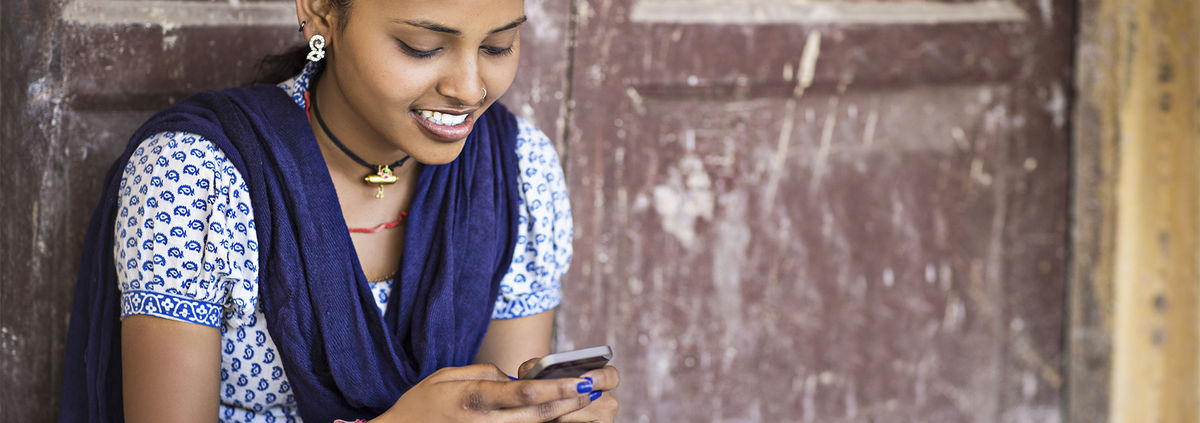 indian girl smiling sending a message on a mobile phone