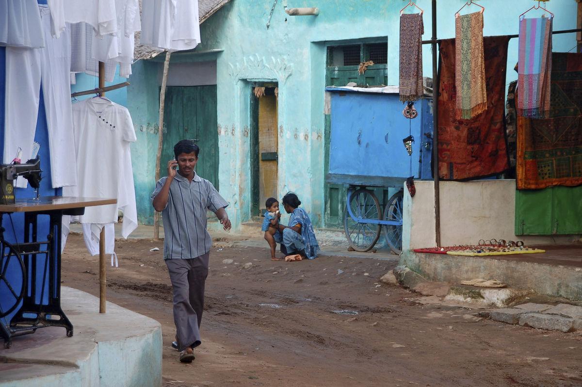 indian man on mobile phone walking down muddy street