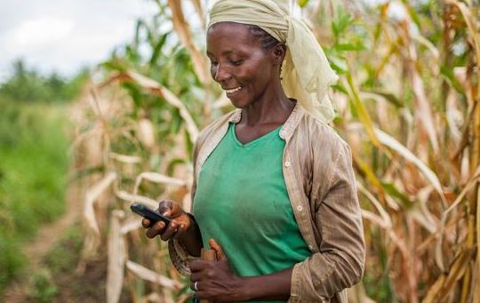 picture of woman smiling holding mobile phone in rural area