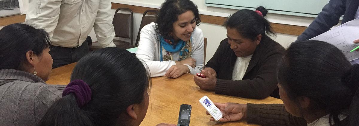 photos from Peru ASBANC pilot-women-around-table-holding-phone