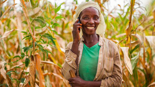 banner image, african woman holding cell phone smiling uganda article