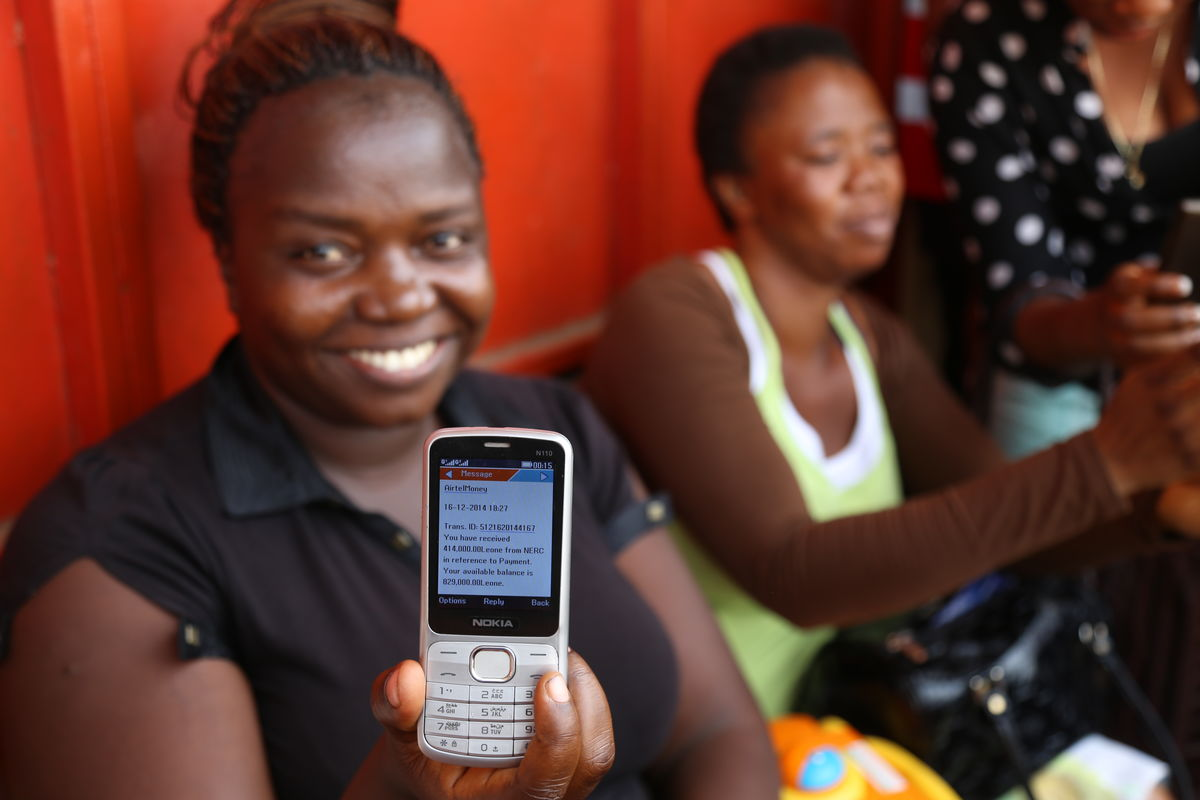a nurse displays her text notification of mobile money in Freetown at UNDP Sierra Leone