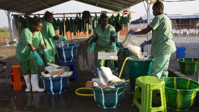 ebola women workers sterilizing boots