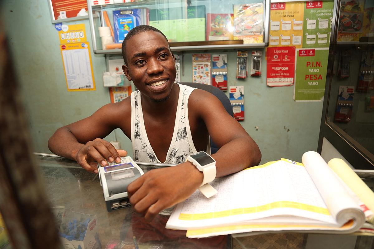 Tanzanian man smiling typing on pos system