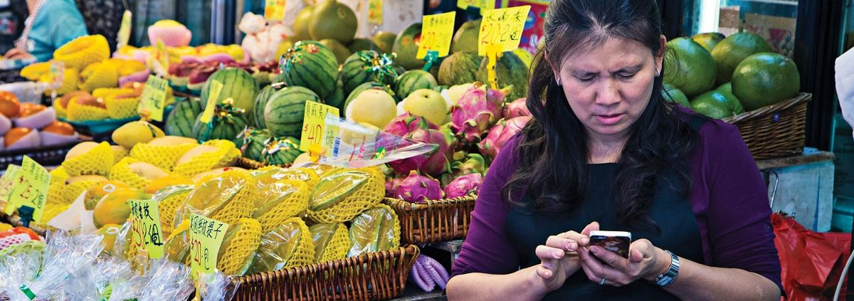 China Woman on the Phone in a Market