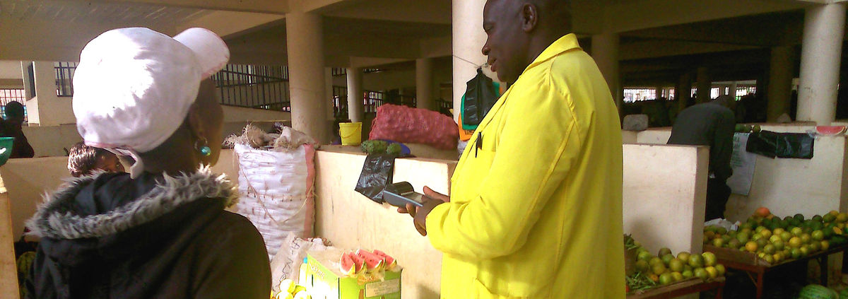 man in Ghana using mobile phone making digital payment at farmers market