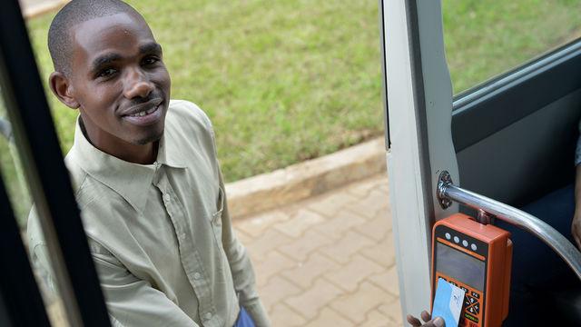 man smiling using digital bus card system in Rwanda – 2
