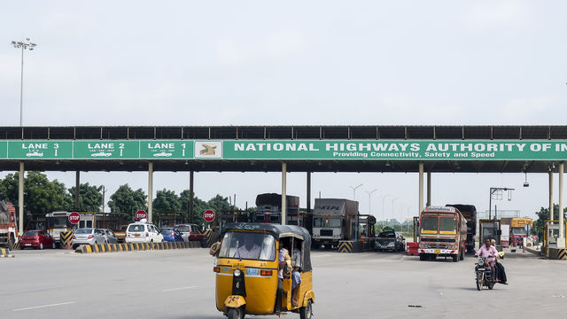 An autorickshaw comes out after paying a toll at a gate on the Bangalore-Hyderabad highway, India.