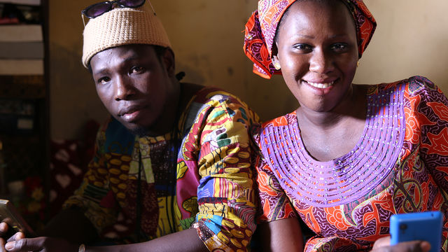 senegalese man and woman smiling holding mobile phones - mame saye diop & hamadi sy benef acmu 2
