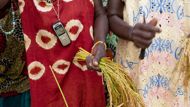 Photo of woman holding crops with phone around her neck